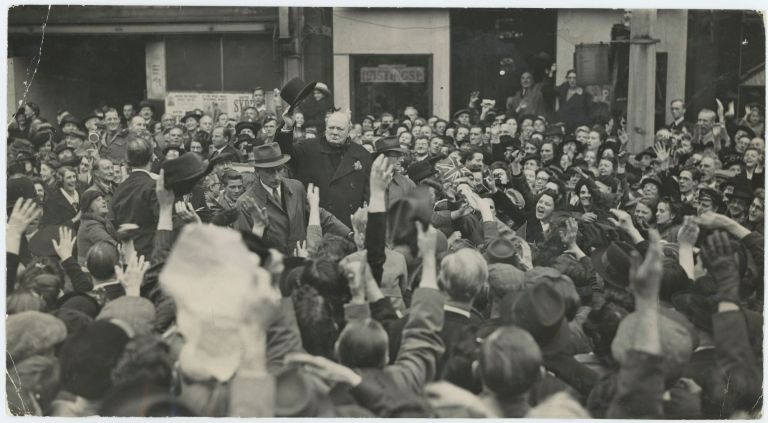 An original wartime press photograph of Prime Minister Winston S. Churchill raising his hat to an animated crowd on 2 July 1945 during a London election tour