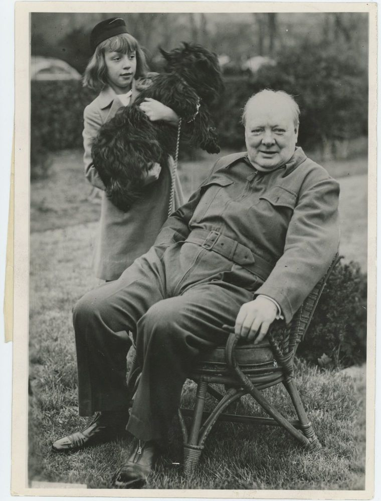 """An original wartime press photograph of Prime Minister Winston S. Churchill wearing his signature """"siren suit"""" on the White House grounds in January 1942, accompanied by FDR's dog and the daughter of presidential advisor Harry Hopkins"""