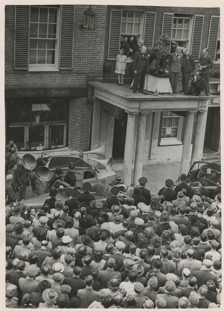 An original wartime press photograph of Prime Minister Winston S. Churchill delivering a campaign speech from a rooftop on 25 June 1945, preparing for the General Election that ended his wartime premiership