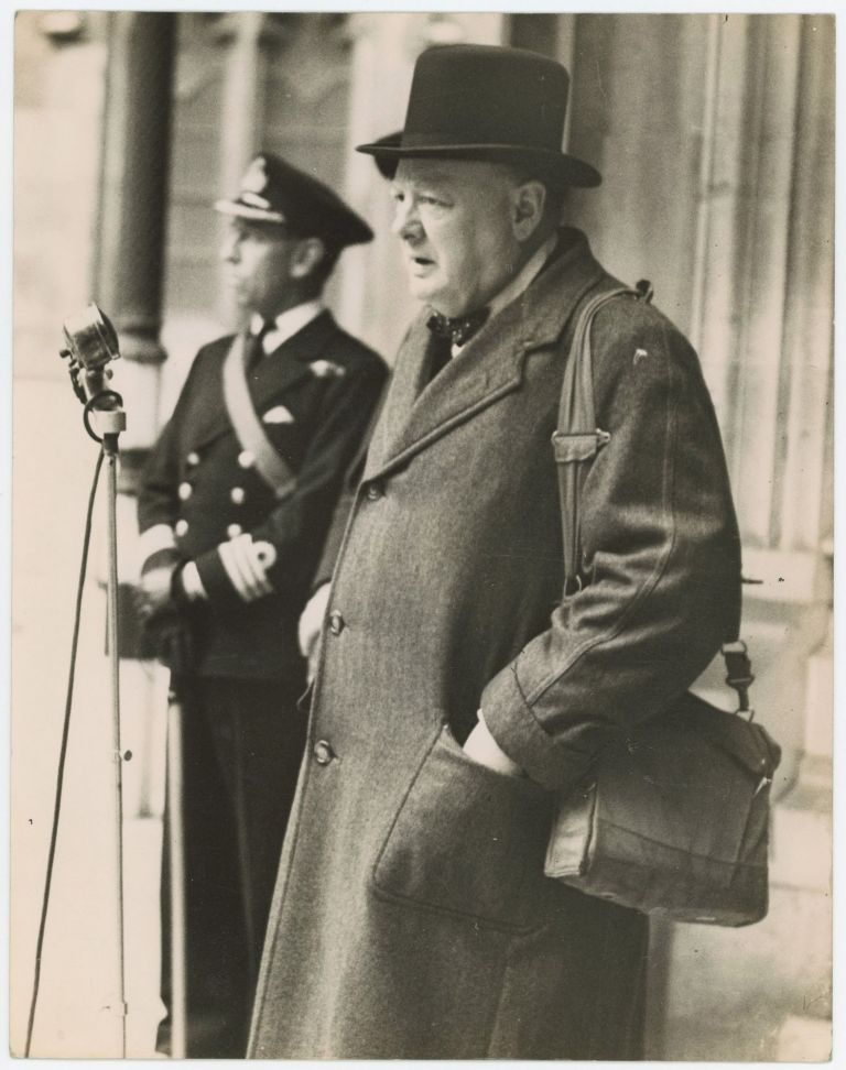 An original wartime press photograph of Prime Minister Winston S. Churchill on 12 May 1942 addressing the Parliamentary Home Guard in London while carrying his gas mask