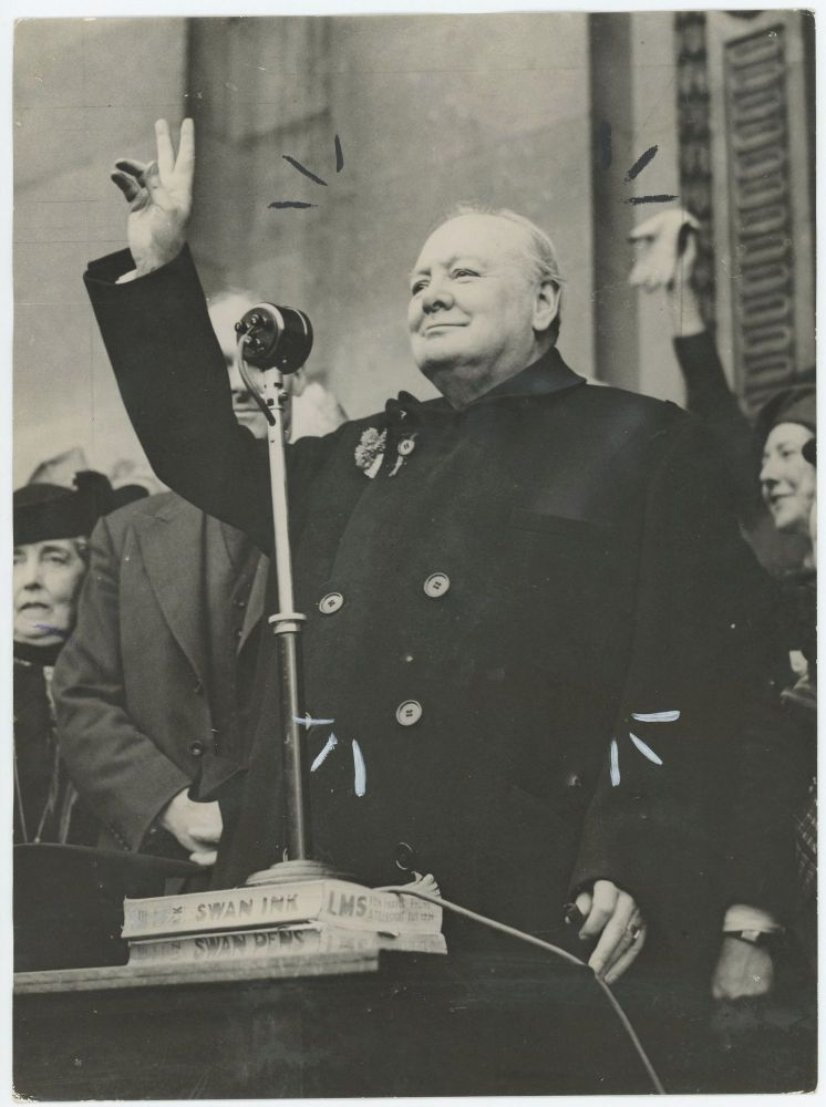 An original wartime press photograph of Prime Minister Winston S. Churchill giving his famous V sign to a crowd as he stands before a microphone during an election tour on 2 July 1945, 24 days before the end of his wartime premiership