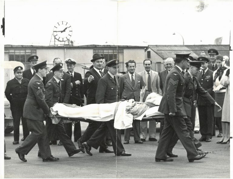 An original press photo of Sir Winston S. Churchill giving the V sign while being carried on a stretcher following his June 1962 fall in Monte Carlo and dramatic flight back to England in an RAF Comet on the orders of Prime Minister Harold Macmillan