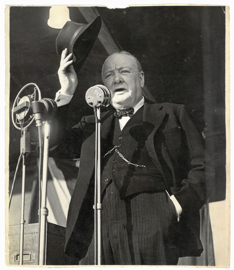 An original wartime press photograph of Prime Minister Winston S. Churchill on 3 July 1945, keeping the sun out of his eyes with a borrowed hat while delivering his final campaign speech for the General Election that ended his wartime premiership