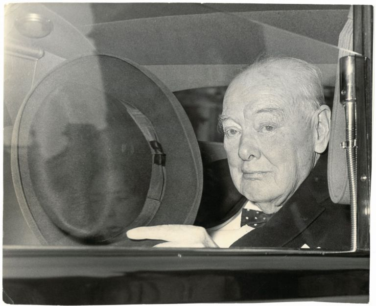 An original press photo of Sir Winston S. Churchill tipping his hat in his car in 1961