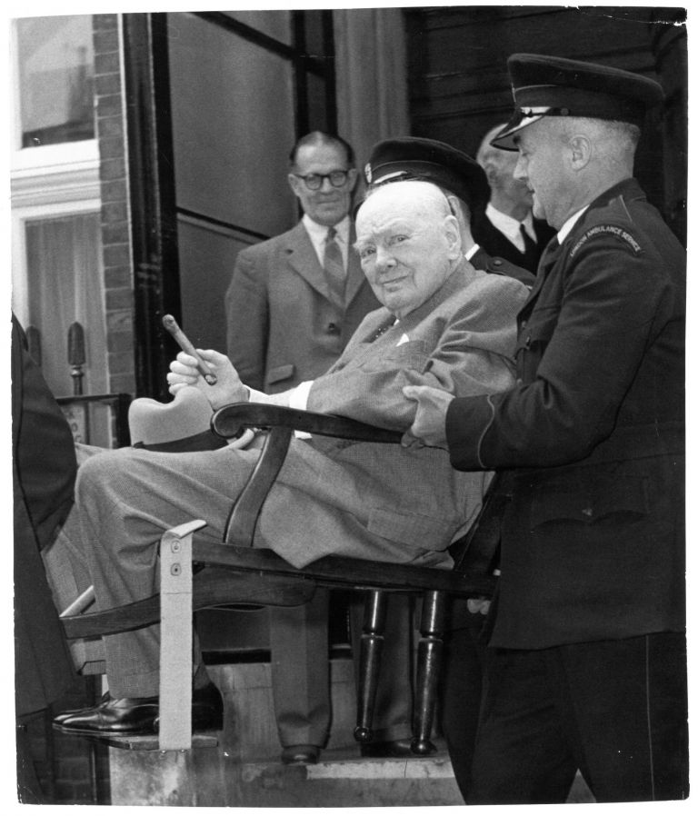 An original press photo of Sir Winston S. Churchill being carried out of Middlesex Hospital on 21 August, 1962, cigar in hand