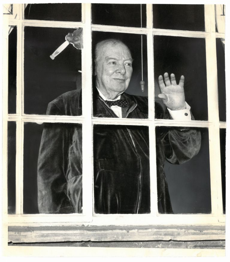 "An original press photo of Sir Winston S. Churchill, wearing a trademark ""siren suit"" and waving from a window of his Hyde Park Gate home on his 89th birthday, 30 November 1963"