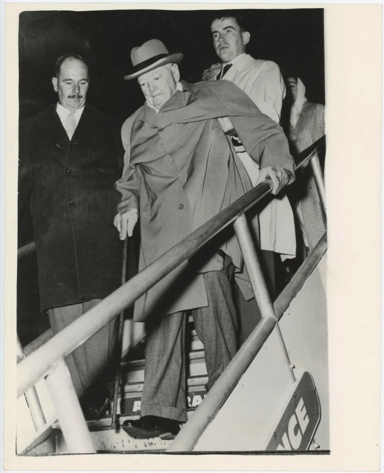 An original press photo of Sir Winston S. Churchill on 29 September 1960 being helped to disembark from the aircraft in which he arrived in Nice for a holiday