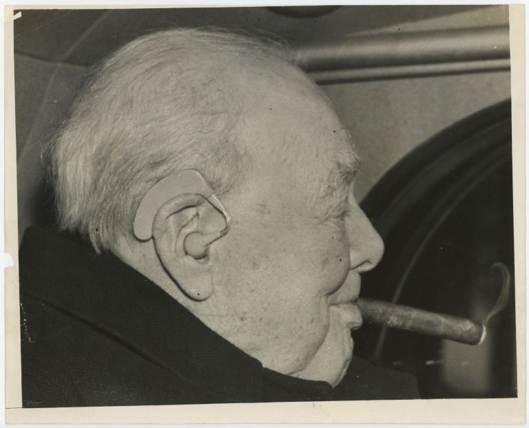 An original press photo of Sir Winston S. Churchill on 9 December 1958 leaving a lunch with Prime Minister Harold Macmillan, Churchill smoking a cigar, his hearing aid prominently visible.
