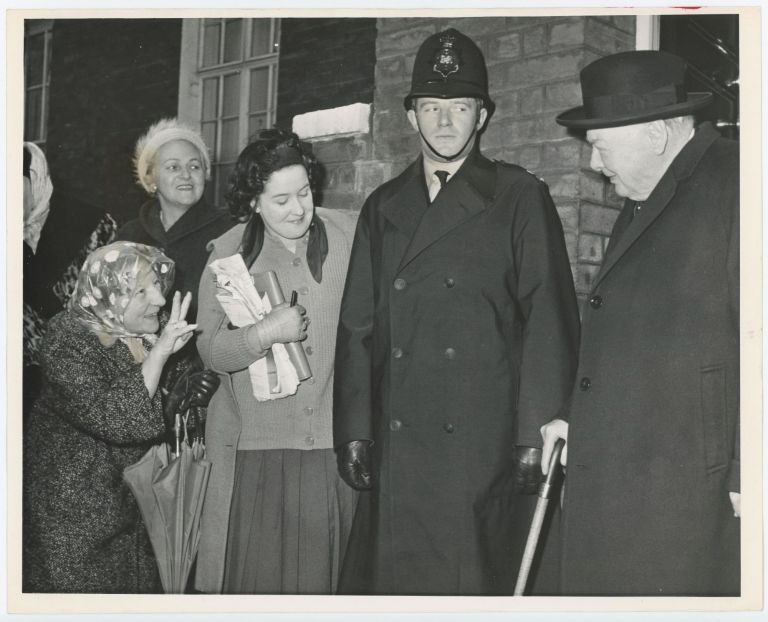 An original press photo of a smiling woman giving Sir Winston S. Churchill his own famous V sign on his 87th birthday, 30 November 1961, as he leaves his Hyde Park Gate home