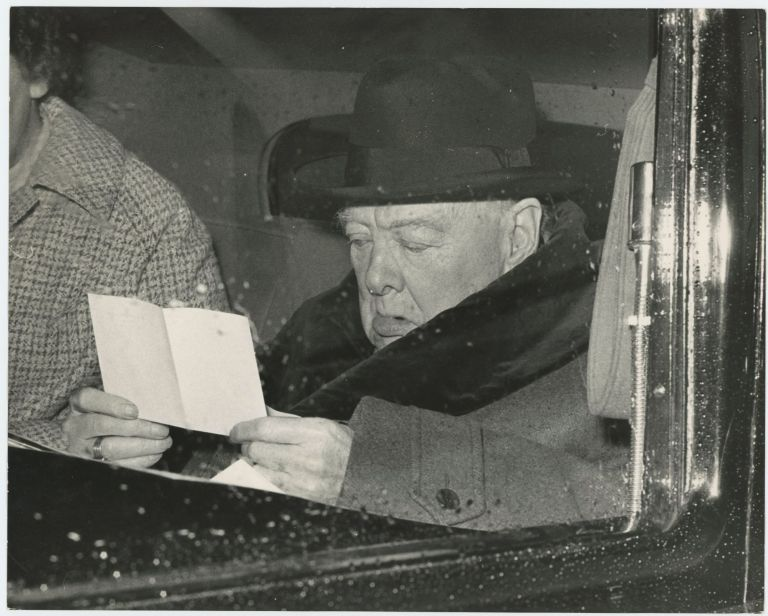 An original press photo of Sir Winston S. Churchill reading a letter on 25 February 1961 as he is driven back to his Hyde Park Gate home from the airport following a holiday on the Riviera
