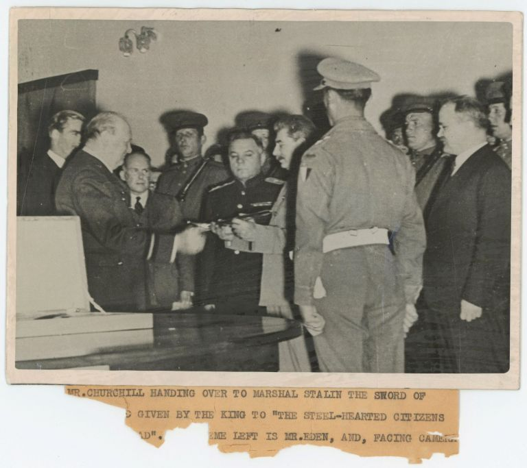 "An original wartime ""British Official Photograph"" capturing British Prime Minister Winston S. Churchill presenting the ""Sword of Stalingrad"" - a gift from King George VI - to Soviet Premier Joseph Stalin on 29 November 1943 during their conference in Tehran with President Franklin Roosevelt"