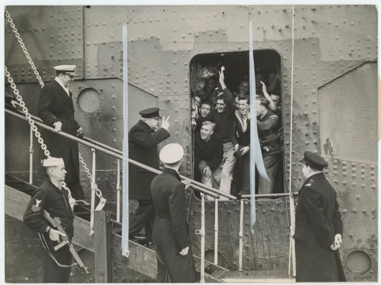 "An original wartime press photograph of Prime Minister Winston S. Churchill in May 1943 giving his ""V"" sign to cheering sailors as he disembarks the Queen Mary in New York after crossing the Atlantic for his third Washington conference with President Roosevelt"