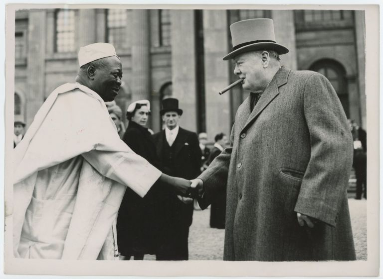 An original press photograph of Prime Minister Winston S. Churchill shaking hands with the Ooni of Ife on 8 June 1953 on the grounds of Blenheim Palace during the Commonwealth Prime Ministers Conference