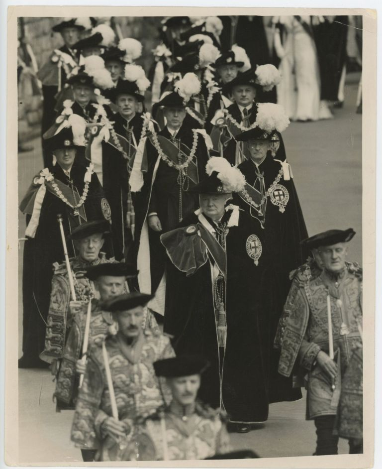 An original press photograph of Prime Minister Sir Winston S. Churchill on 14 June 1954 wearing his robes and insignia and marching at the head of his fellow Companions after his investiture by Queen Elizabeth II as a Knight Companion of the Most Noble Order of the Garter