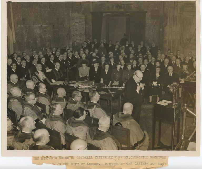 An original wartime press photograph of Prime Minister Winston S. Churchill in London's ancient, war-damaged Guildhall speaking upon receiving the Honorary Freedom of the City of London on 30 June 1943