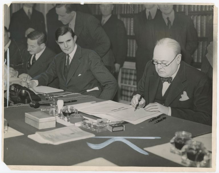 An original wartime press photograph of Prime Minister Winston S. Churchill signing the Lend Lease agreement on 11 March 1941 beside U.S. Ambassador to Britain Gil Winant