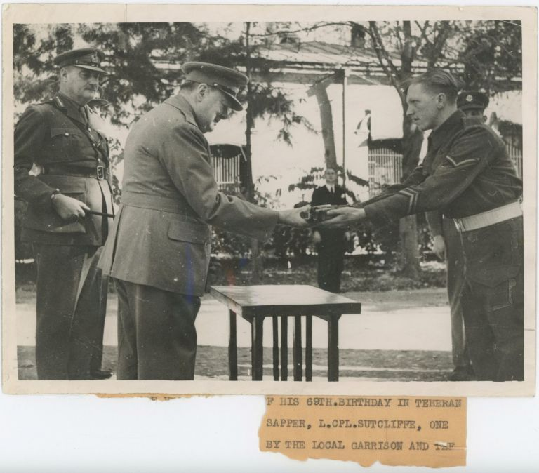 An British Official wartime press photograph of Prime Minister Winston S. Churchill receiving a gift from a British soldier during the Tehran Conference with Stalin and Roosevelt on 30 November 1943, Churchill's 69th birthday