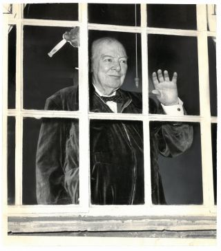 "An original press photo of Sir Winston S. Churchill, wearing a trademark ""siren suit"" and waving..."