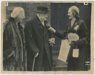 An original press photo of Winston S. Churchill and Lady Clementine Churchill purchasing a...
