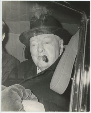 An original press photo of Sir Winston S. Churchill on 4 April 1960 smoking a cigar on his way to...