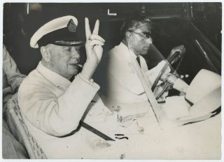An original press photograph of Sir Winston S. Churchill flashing his famous V sign while being...