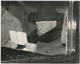An original press photo of Sir Winston S. Churchill reading a letter on 25 February 1961 as he is...