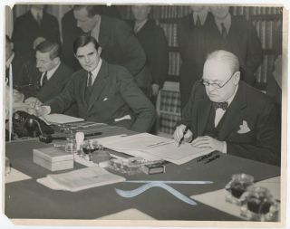An original wartime press photograph of Prime Minister Winston S. Churchill signing the Lend...